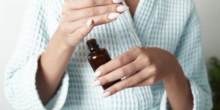 Woman using serum with dropper