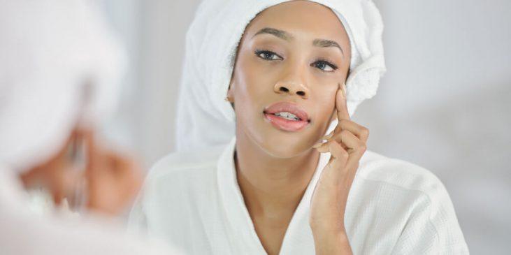 Woman looking at skin in mirror