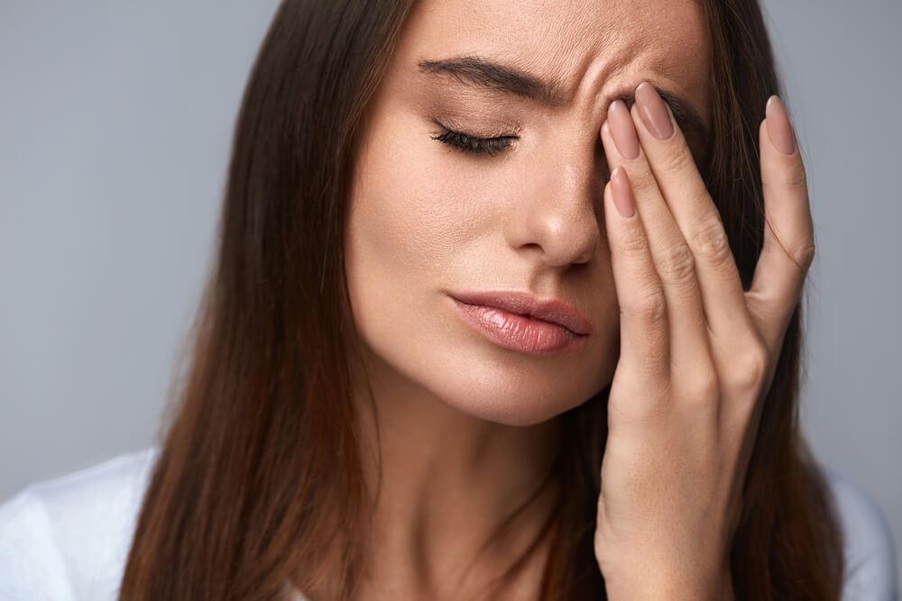 Woman rubbing face
