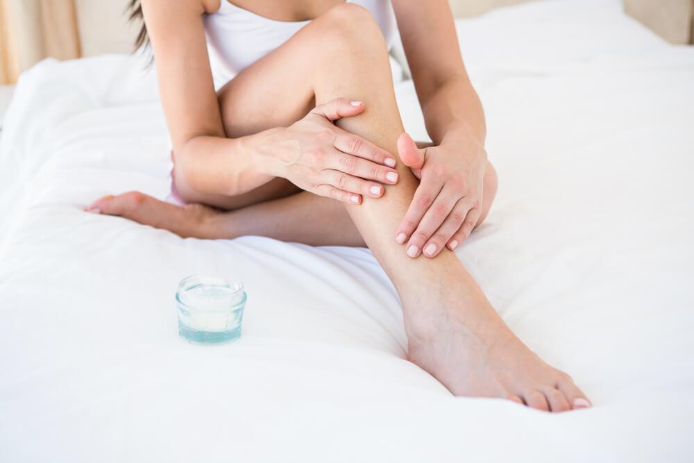Woman applying cream to legs