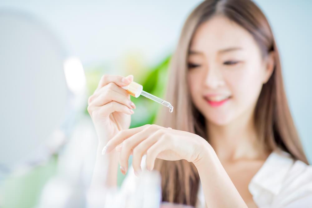 Woman applying serum to hand
