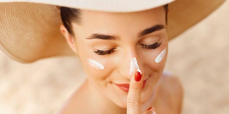 Woman using skin cream in summer