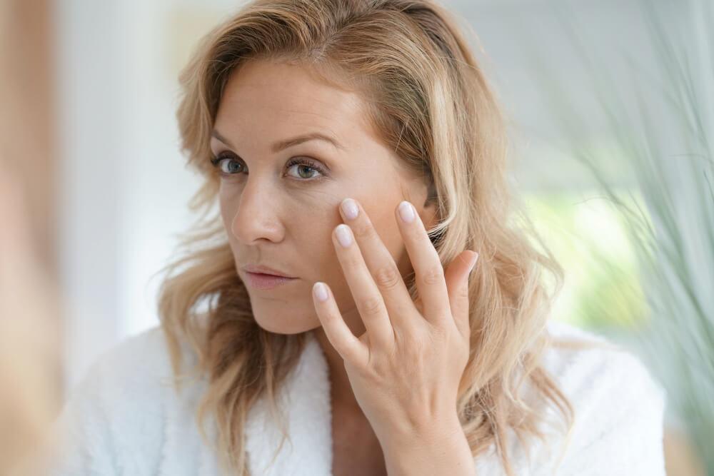 Woman looking at wrinkles in mirror